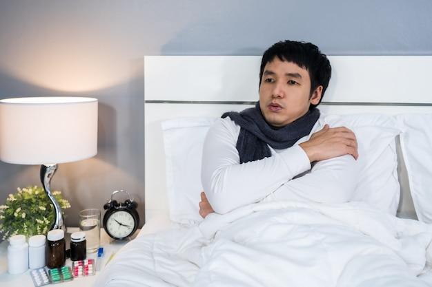 Kranker mann, der sich im bett kalt fühlt