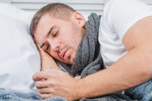 Kranker mann, der starken schal um seinen hals betrachtet thermometer trägt