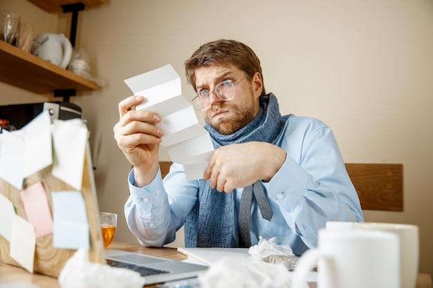 Kranker mann, der verschreibungspflichtige medizin liest, die im büro arbeitet, erwischte geschäftsmann erkältung, saisonale grippe. pandemie influenza, krankheitsvorbeugung, krankheit, virus, infektion, temperatur, fieber und grippe konzept
