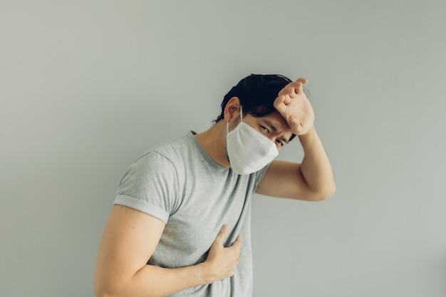Kranker mann, der weiße hygienemaske im grauen t-shirt im konzept des virus trägt.