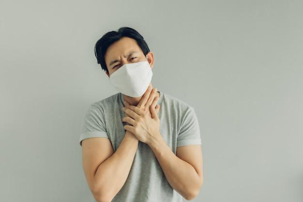 Kranker mann, der weiße hygienemaske im grauen t-shirt trägt