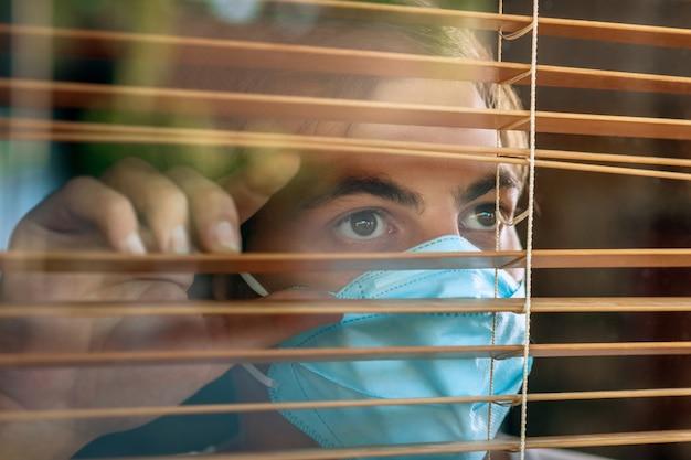 Kranker mann des koronavirus, der durch das fenster schaut und maskenschutz und erholung von der krankheit zu hause trägt. quarantäne.