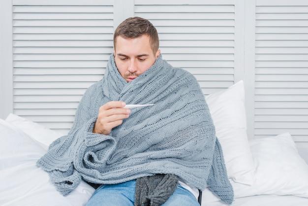 Kranker mann eingewickelt im schal, der thermometer betrachtet
