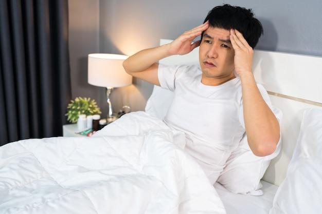 Kranker mann hat kopfschmerzen im bett