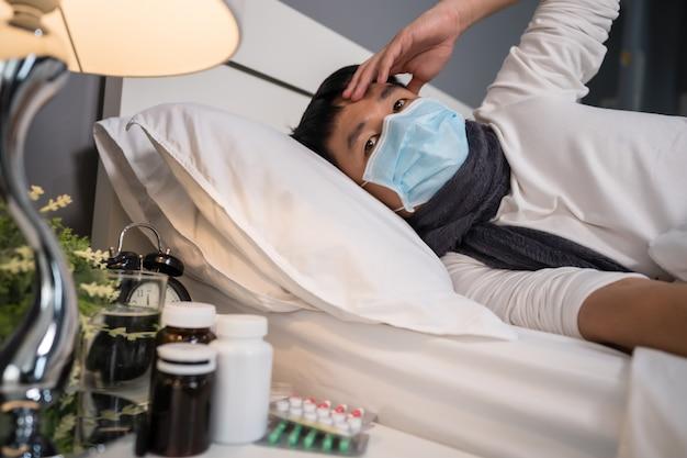 Kranker mann in der medizinischen maske ist kopfschmerzen und leidet an viruskrankheit und fieber in einem bett, coronavirus-pandemie-konzept.