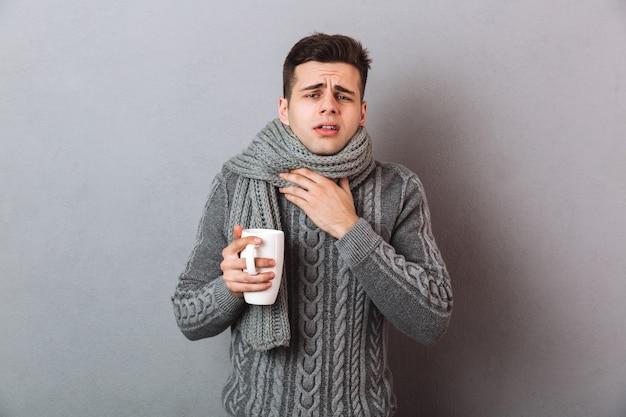 Kranker mann in der strickjacke und in schal, die halsschmerzen beim halten der tasse tee haben