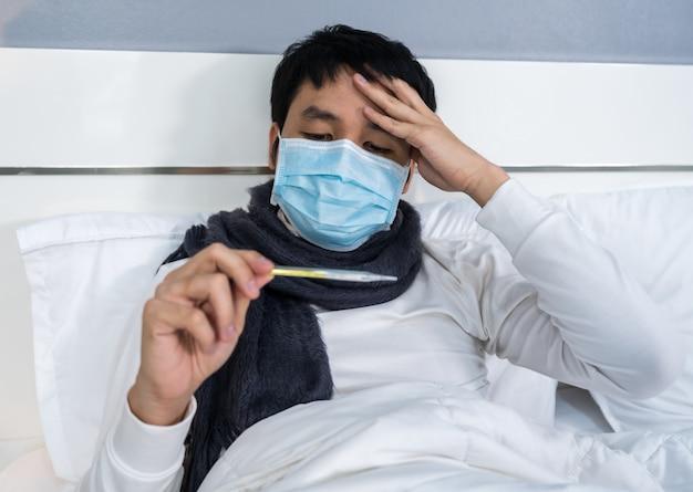 Kranker mann in medizinischen maskenkopfschmerzen und unter verwendung eines thermometers, um seine temperatur auf dem bett zu überprüfen, coronavirus-pandemiekonzept.
