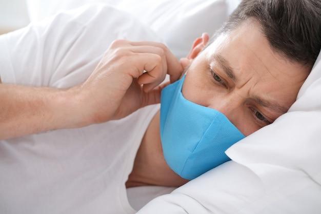 Kranker mann in medizinischer schutzmaske zu hause