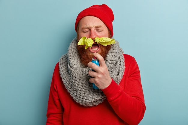Kranker mann in warmer kleidung mit papiertaschentüchern in der nase und spray gegen halsschmerzen