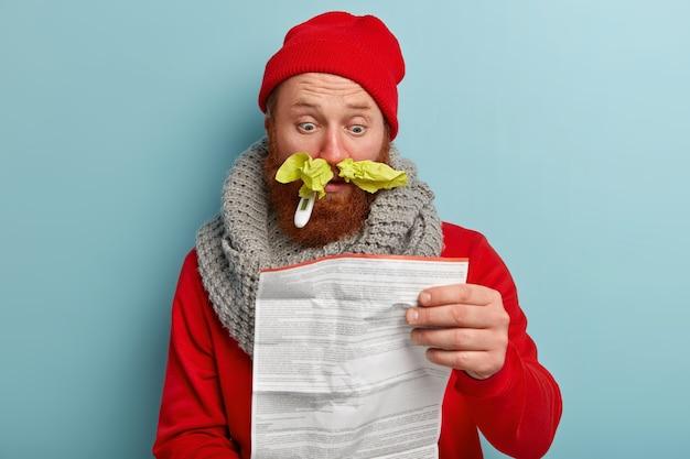 Kranker mann in warmer kleidung mit papiertaschentüchern und thermometer