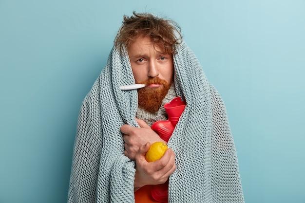 Kranker mann in warmer kleidung mit thermometer, hält zitrone, wärmflasche