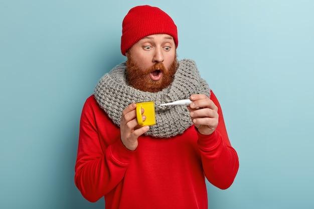 Kranker mann in warmer kleidung mit thermometer und tasse