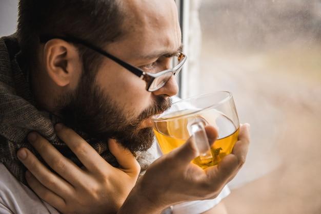 Kranker mann mit einem schal um den hals, der zu hause am fenster tee trinkt