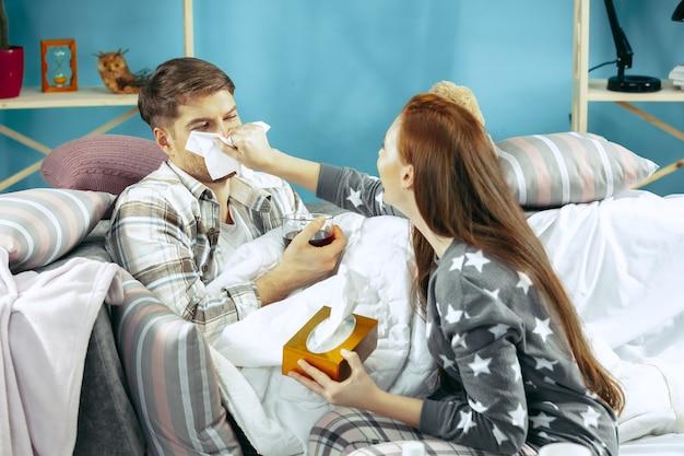 Kranker mann mit fieber, das im bett liegt und temperatur hat. die seine frau kümmert sich um ihn.