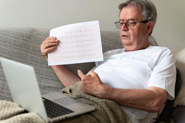 Kranker mann mit mittlerem schuss auf der couch mit laptop