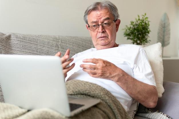 Kranker mann mit mittlerem schuss auf der couch