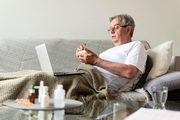 Kranker mann mit mittlerem schuss, der auf der couch sitzt