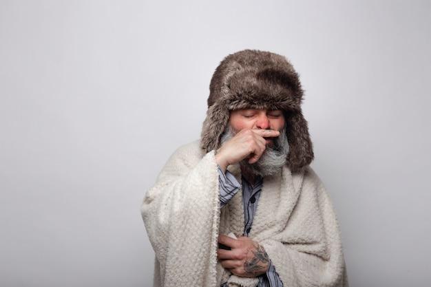 Kranker mann mit mütze und decke über der nase beim niesen
