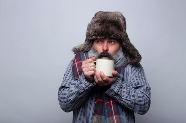 Kranker mann mit pyjama und mütze bläst eine tasse heißen tee