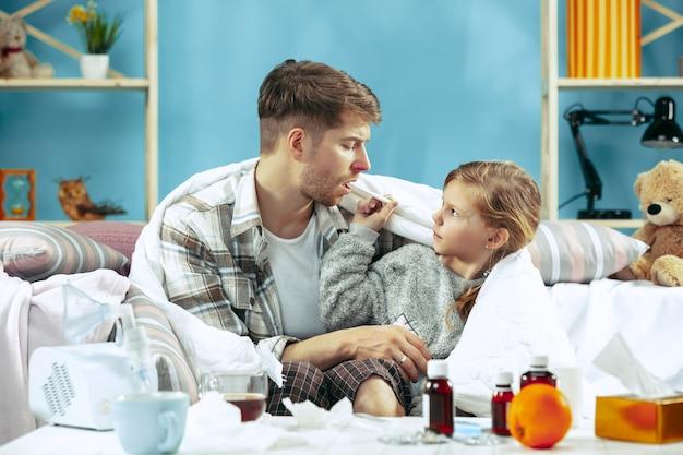 Kranker mann mit tochter zu hause. behandlung zu hause. mit einer krankheit kämpfen. medizinische gesundheitsversorgung. familienhaftigkeit. der winter, influenza, gesundheit, schmerz, elternschaft, beziehungskonzept. entspannung zu hause