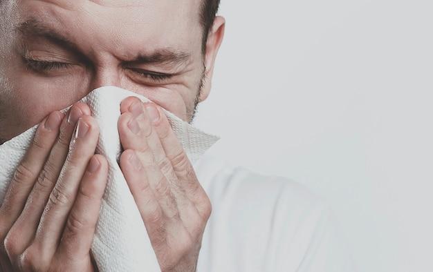 Kranker mann niest in papiertaschentuch