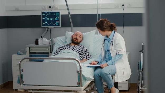 Kranker mann ruht im bett mit sauerstoffschlauch im gespräch mit arzt und erklärt krankheitssymptome