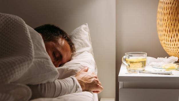 Kranker mann schläft im bett mit hohem fieber, leidet an grippe, tasse tee mit zitrone auf dem tisch