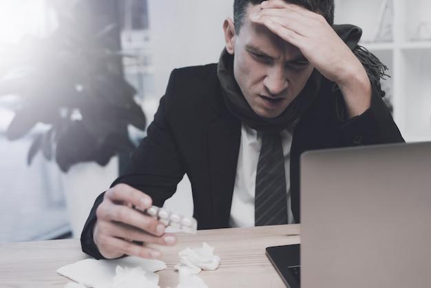 Kranker mann sitzt in seinem büro und hält ihren kopf.