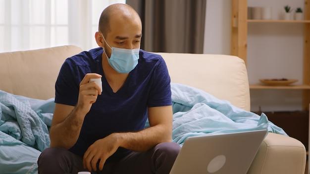 Kranker mann zu hause, der online mit seinem arzt spricht und eine flasche mit pillen hält