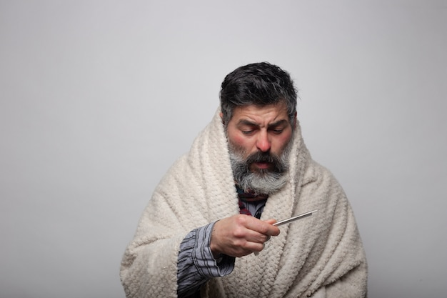 Kranker reifer mann, der den thermometer eingewickelt in einer decke betrachtet