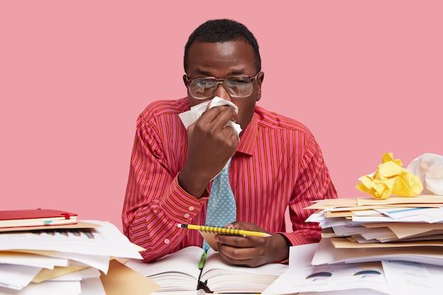 Kranker schwarzer männlicher arbeiter hat laufende nase, benutzt taschentuch, arbeitet im coworking space, hält spiralblock mit bleistift, muss die arbeit beenden, isoliert über rosa raum