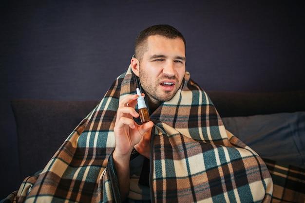 Kranker und kranker junger mann hält nasenspray in händen. er schrumpft, schaut aber vor die kamera. guy wird niesen. er sieht schlecht aus. mann sitzt im schlafzimmer.