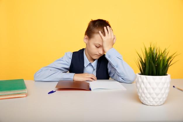 Kranker und müder schuljunge, der am schreibtisch sitzt und lernt.