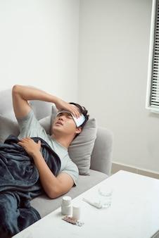 Kranker verschwendeter mann, der auf dem sofa liegt und an erkältung und wintergrippevirus leidet, der medizintabletten im gesundheitskonzept hat und die temperatur auf dem thermometer sieht