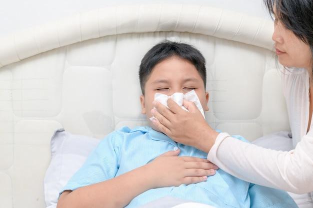 Krankes asiatisches kind, das nase mit gewebe abwischt oder säubert