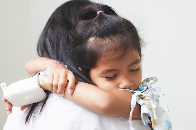 Krankes asiatisches kindermädchen, das iv lösung verbunden haben, ihre mutter mit liebe im krankenhaus umarmend