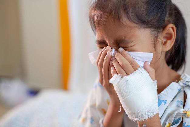 Krankes asiatisches kindermädchen, das iv lösung verbunden haben, nase mit gewebe auf ihrer hand im krankenhaus abwischend und zu säubern