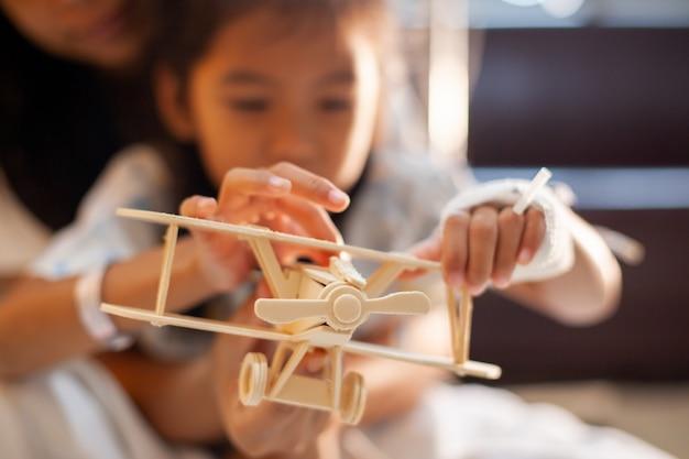 Krankes asiatisches kindermädchen, das mit hölzernem flugzeug des spielzeugs mit ihrer mutter während aufenthalt im krankenhaus spielt