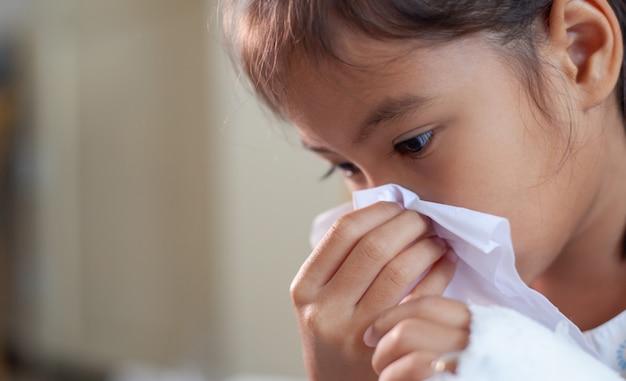 Krankes asiatisches kindermädchen, das nase mit gewebe auf ihrer hand im krankenhaus abwischt und säubert