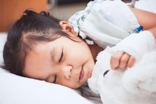 Krankes asiatisches kindermädchen schläft im krankenhaus