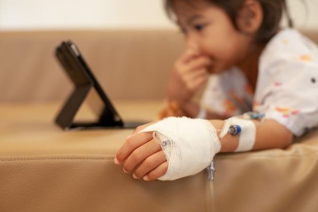 Krankes asiatisches kleines kindermädchen, das iv lösung verbunden hat, digitale tablette spielend