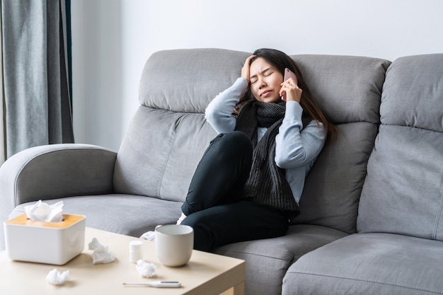 Krankes asiatisches mädchen, das zu hause auf dem sofa im wohnzimmer sitzt und mit dem arzt oder ihrer familie auf dem handy zur beratung spricht, freier platz. konzept für erkältung, grippe, coronavirus-pandemie oder heimisolierung.
