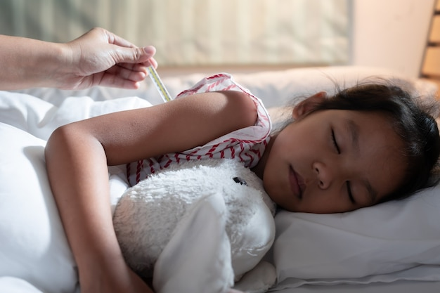 Krankes asiatisches mädchen schläft auf dem bett und ihre mutter überprüft ihre körpertemperatur