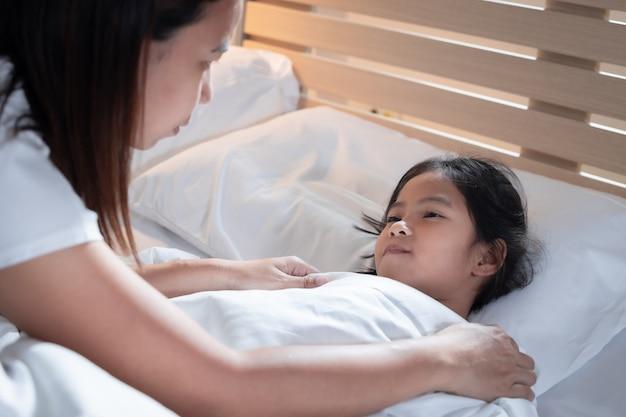 Krankes asiatisches mädchen wird krank und schläft auf dem bett, mutter kümmert sich und bedeckt die decke ihrer tochter