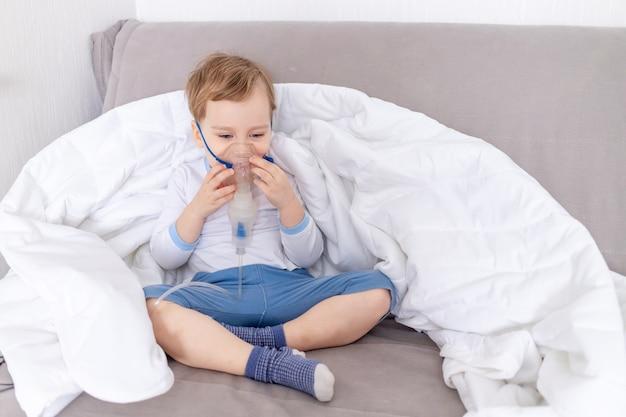 Krankes baby mit inhalator behandelt den hals zu hause, das konzept der gesundheits- und inhalationsbehandlung