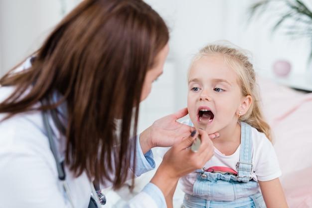 Krankes kind, das den mund öffnet, während arzt betrachtet, der ihre halsschmerzen mit medizinischem werkzeug untersucht