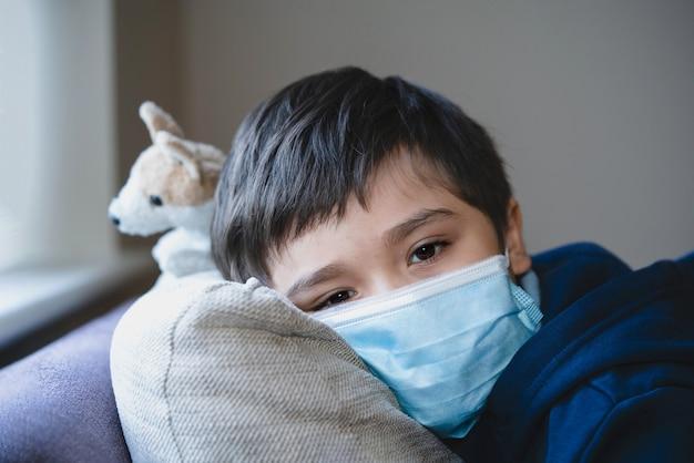 Krankes kind, das eine schutzmaske trägt, krankes kind in einer medizinischen gesichtsmaske, die kopf auf sofa mit traurigem gesicht liegt