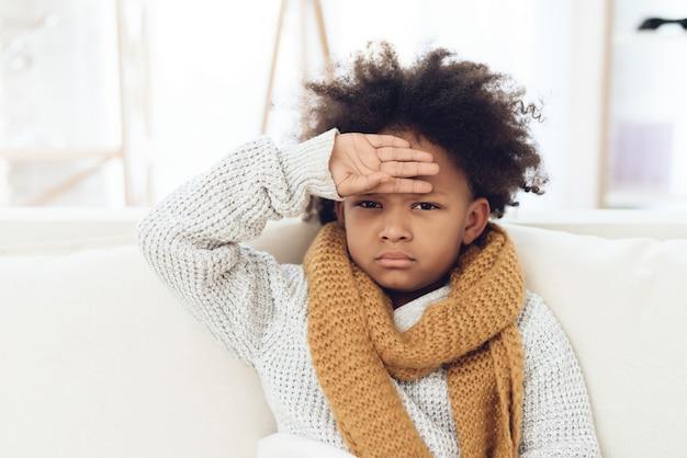 Krankes kind mit der grippe, die zu hause auf couch sitzt.