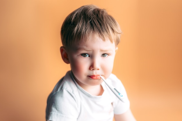 Krankes kind mit einem thermometer in seinem mund mit traurigem gesicht auf orange hintergrund