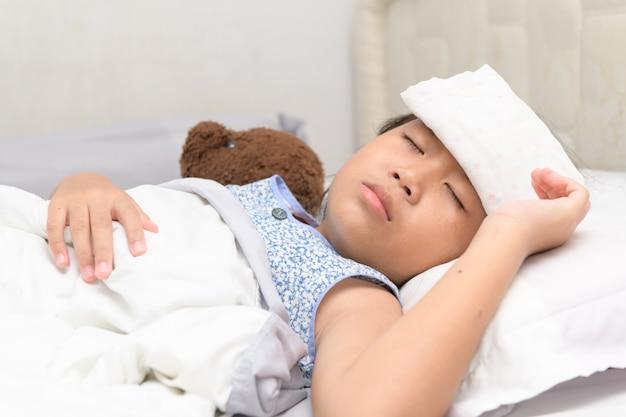 Krankes kind mit hohem fieber im bett.